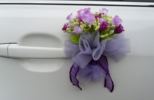 На ручке свадебного автомобиля бутоньерка